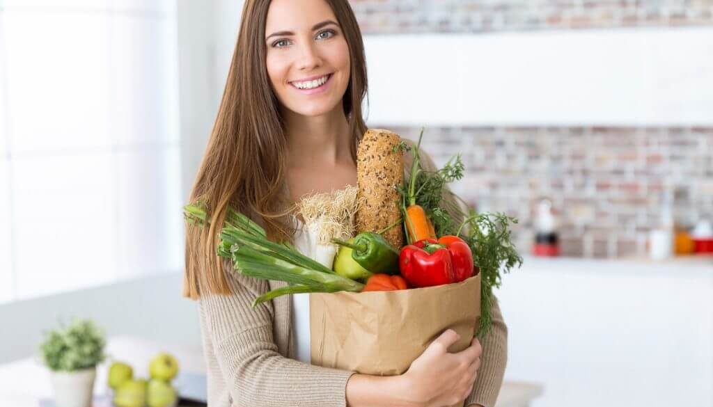 Beautiful young woman with vegetables in grocery bag at home.