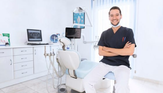 Portrait of a happy confident dentist in clinic